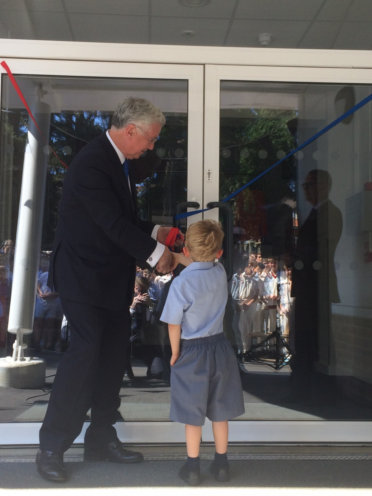 Michael cutting the ribbon to the new New Beacon Centre with a young boy from reception