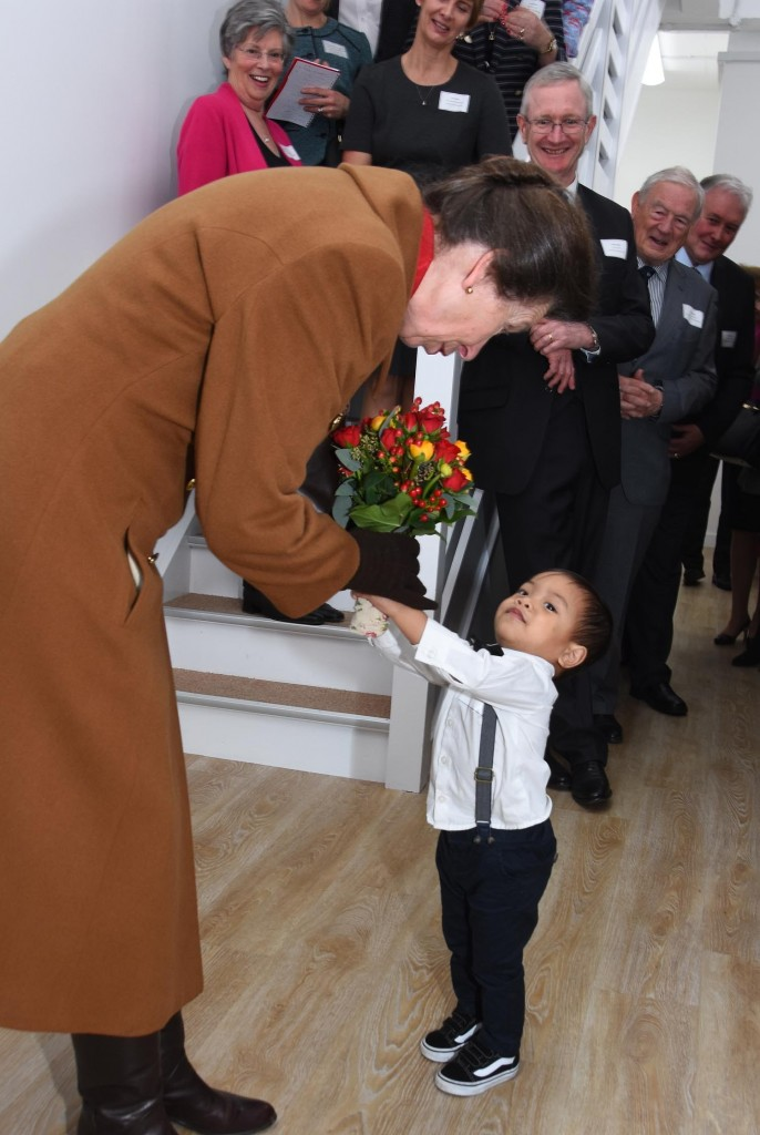 A boy reluctantly hands HRH flowers
